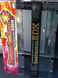IIDX 18 and IIDX 1st Style marquees leaned sideways against the front of a beatmania IIDX machine