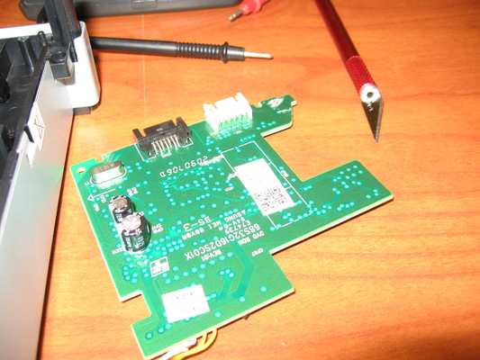 A Lite-On 83850c v2 controller PCB removed from its drive. Several traces are severed by a nearby blade.