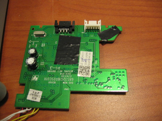 The PCB with trace repairs insulated by electrical tape.