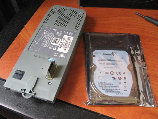Stock hard drive in its shell next to the replacement drive in an antistatic bag.