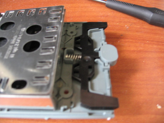 Reassembly of the metal drive cage, latch spring, and plastic case.