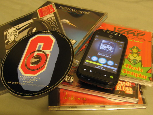 My HTC Espresso listening to Rock the House over Subsonic, sitting on a pile of CD jewel cases next to the Rock the House CD single.