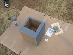 Subwoofer cabinet outside on a sheet of cardboard receiving its first coat of primer.