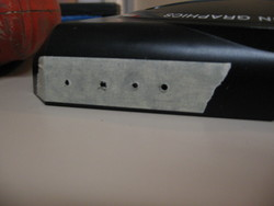 Pilot holes for the four new AV connectors drilled through the marked masking tape on the rear of the case.