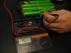 Testing the replacement pack with a multimeter. It reads 10.47VDC.